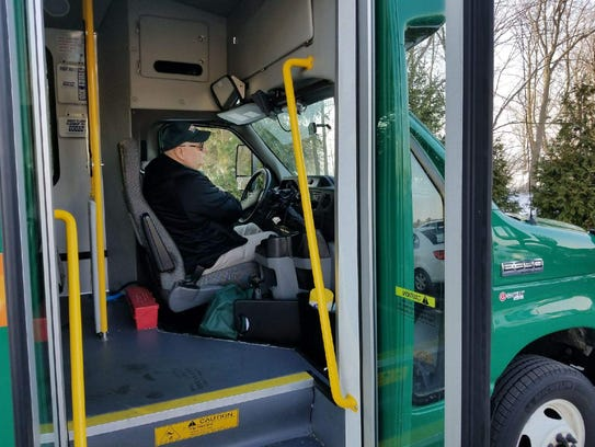 TRIPS driver Bill Voelker opens the door to let passengers
