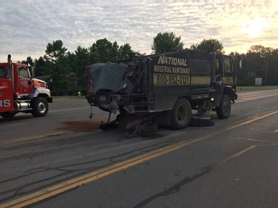 A street sweeper that was hit from behind by a Suburban