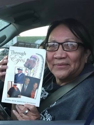 """Wanda Bear Medicine-Peterson holds a copy of her new book """"Through My Eyes"""" about her father's life and wisdom."""