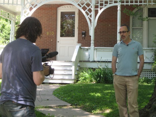 Don Argott, left, films Robert Weide on June 15 at 800 N. Van Buren St., the house in which the writer Kurt Vonnegut lived during his time teaching at the Iowa Writers' Workshop.