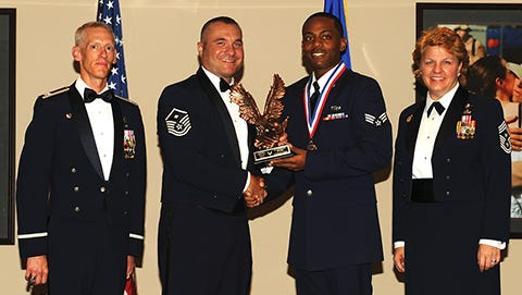 Col. Christopher Bennett, far left, 19th Airlift Wing vice commander, along with Chief Master Sgt. Rhonda Buening, far right, 19th AW Command Chief and Master Sgt. Jason Crouse, 19th Security Forces Squadron first sergeant, left, congratulate Senior Airman Jamaar Jackson during the graduation ceremony.