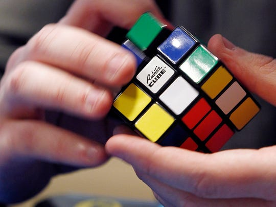 A young competitor tries to solve a Rubik cube puzzle during the French Rubik's cube championships, on April 20, 2012 in Paris.