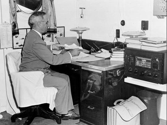 In this Aug. 6, 1945, file photo aboard the cruiser USS Augusta, President Harry Truman, with a radio at hand, reads reports of the atomic bomb raid of Hiroshima, Japan, while en route home from the Potsdam Conference.