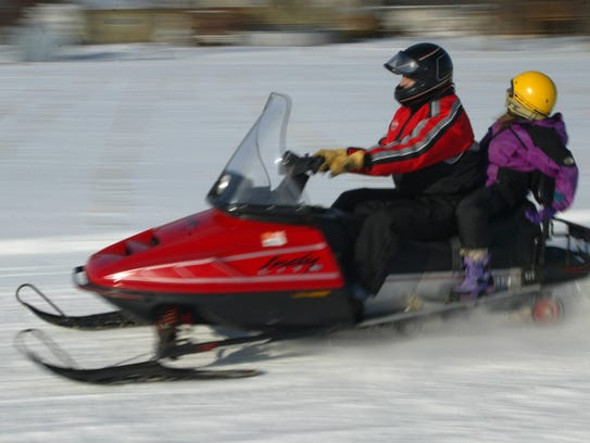 Two people whiz past the scenery on a snowmobile trail
