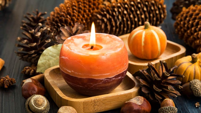 Autumn candle decoration with cones,moss,cinnamon sticks, acorns,anise and pumpkins