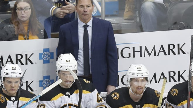 Boston Bruins head coach Bruce Cassidy works behind his team during a game against the Pittsburgh Penguins, Sunday, Jan. 19.