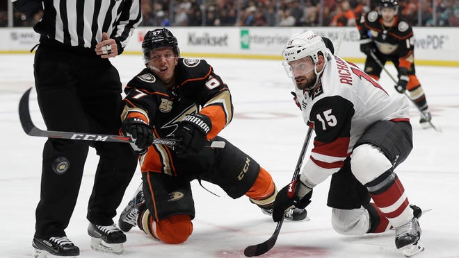 Anaheim Ducks' Rickard Rakell, left, faces off against Arizona Coyotes' Brad Richardson (15) during the second period of an NHL hockey game Wednesday, Oct. 10, 2018, in Anaheim, Calif. (AP Photo/Marcio Jose Sanchez)