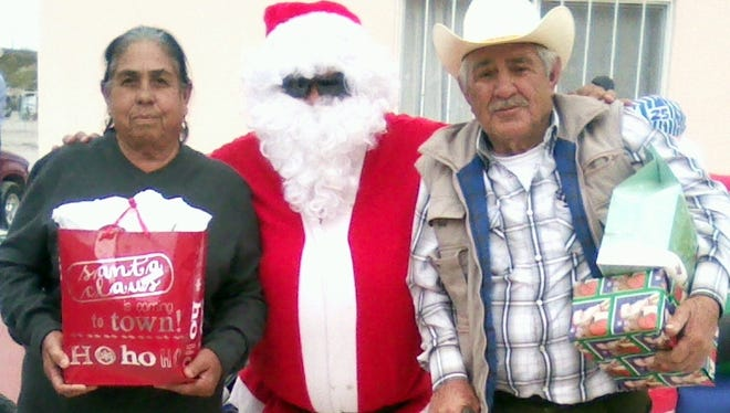 """Santa Claus paid a visit to the villagers of San Pedro de Conchos and the surrounding pueblos high in the hills of Chihuahua, Mexico just in time for Christmas. The jolly man in the red suit was helped along by Esperanza Lozoya who provides humanitarian aid to the villagers who have no electricity, but do have running water. There are about 70 residents of San Pedro de Conchos – mostly the elderly – who enjoyed a day of celebration and sharing Christmas gifts that were provided through local donations in Deming and Columbus. Lozoya and volunteers collected gifts that were placed under the """"Tree of Hope."""" Trees were set up at Peppers Supermarket, Diaz Farms Produce and San Jose Grocery. Lozoya would like to thank all those who contributed and donated to the cause so that the villagers could enjoy a Christmas gift."""