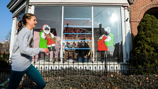 A woman runs by as Sarah Kreiser, a volunteer with the Annville Free Library, decorates the window of 209 E. Main St., Annville, to promote the library's holiday fund drive. This is the second year the library decorated windows to help spread its message and a little holiday cheer, explained Nancy Smith, a library board member. The library will also decorate the windows at the Batdorf Restaurant, 245 W. Main St. The library, at 216 E. Main St., hopes to raise money for new books; a new program, such as Lego Night for Kids; and a new refrigerator.