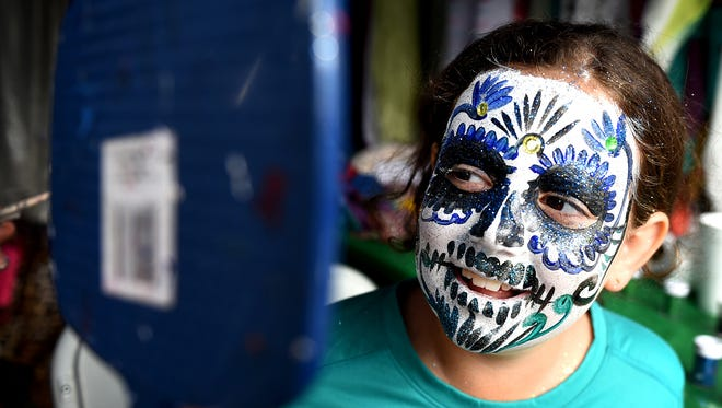 Breana Yodis, 9, looks at her painted face created by artist Jose Vera during the El Dia de los Muertos celebration on Saturday, Oct. 24, 2015 at Cheekwood.