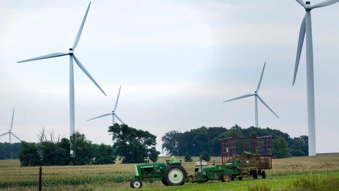 A farmer bales hay near wind turbines in 2014 in northeastern Fond du Lac County.