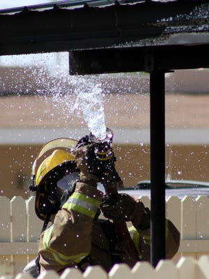 Firefighters from the Alamogordo Fire Department extinguish the remnants of a structure fire Thursday afternoon on Fourth St.