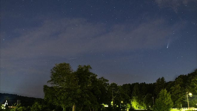 Comet NEOWISE is seen near the Old Stone Church, bottom left, in West Boylston on Sunday