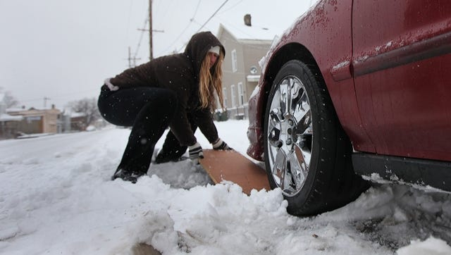 Debbie Agee uses the leaf from a kitchen table to give a friend's stuck car some traction.