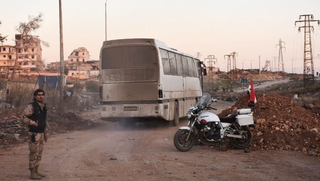 A bus drives through the Syrian government-controlled crossing of Ramoussa, on the southern outskirts of Aleppo, on Dec. 18.