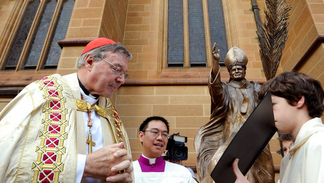 FILE - In this May 1, 2011 file photo, Cardinal George Pell, left, reads a bible during the blessing of a statue of John Paul ll at St Mary's Cathedral in Sydney, Australia. Australian police say they are charging Pell with historical sexual assault offenses.
