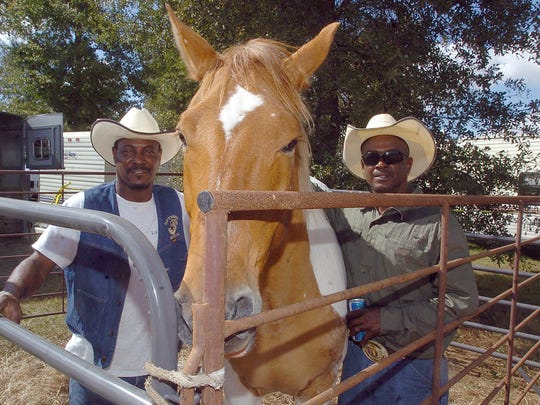 Daily World File photo William Darby, of Youngsville, left, and Scottie Green, of Gueydan, take care of their horse at the 2014 Step-N-Strut Trail Ride.