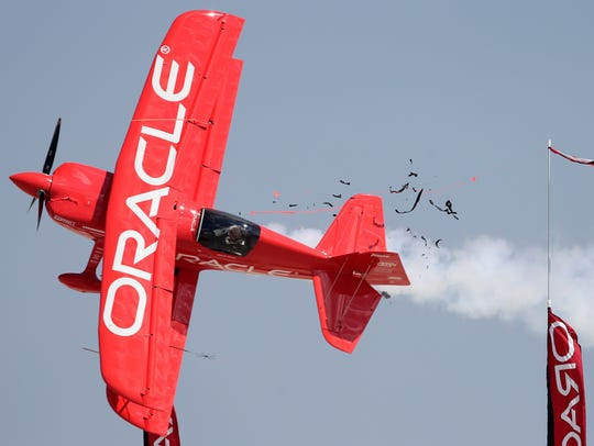 Sean D. Tucker cuts a ribbon during the afternoon airshow