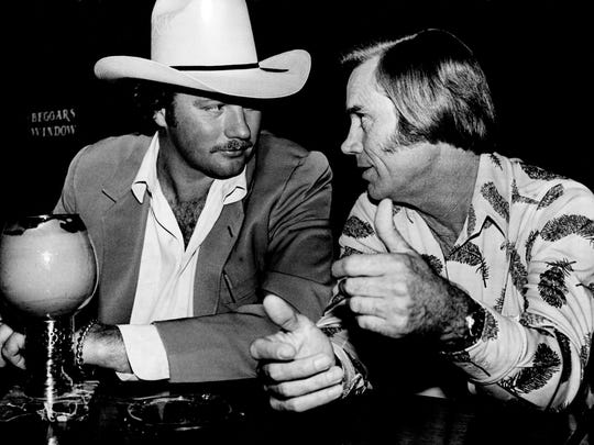 """Billy Bob Barnett, left, and George Jones discuss their new management agreement during dinner at the Stockyard restaurant. Barnett, a former pro football player, owns """"Billy Bob's Texas,"""" a Fort Worth nightclub said to be the largest in the world."""