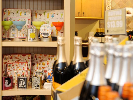 A new display shows glasses, books and other merchandise as West Meade Wine and Liquor Mart prepares to begin selling other items along with its vast selection of wine and other alcohol.