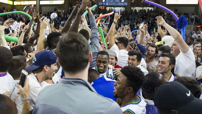 Florida Gulf Coast University sophomore, Zach Johnson, center, smiles in celebration as fans rush the court following the ASUN Championship Final against the University of North Florida at Alico Arena in Estero, Florida on Sunday, March 5, 2017. The Eagles defeated the Ospreys 77-61.