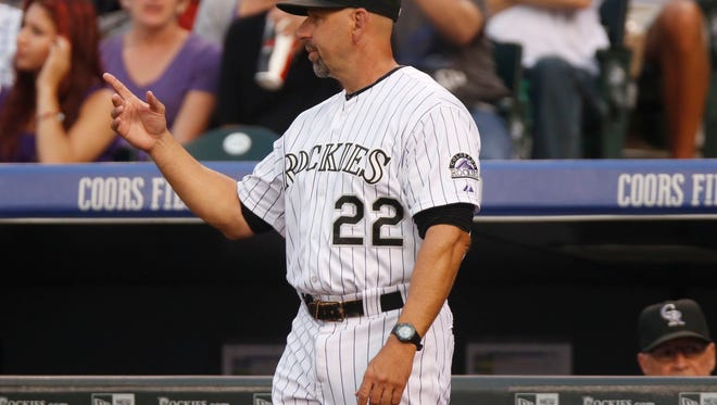 Colorado Rockies manager Walt Weiss points to the bullpen to call in relief pitcher Justin Miller to replace starting pitcher Chris Rusin who gave up a double to New York Mets' Curtis Granderson  in the third inning of a baseball game Saturday, Aug. 22, 2015, in Denver. (AP Photo/David Zalubowski)