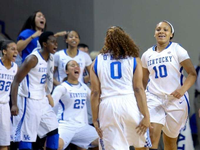 Kentucky's Bernisha Pinkett let's out a small smile, to teammate Jennifer O'Neil, after sinking a three-point shot.  The Wildcats defeated the Cardinals 69 to 64.  Dec. 1, 2013
