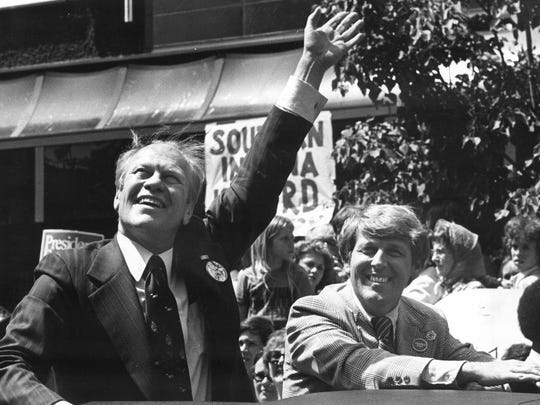 Gerald Ford waves during the presidential motorcade