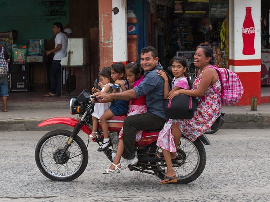 A family rides on a motorcycle in Tecun Uman, Guatemala. last month. Many immigrants cross into Mexico from this border town. Crime and lack of jobs have sent people from Central America to the U.S. including unaccompanied minors in increasing numbers.