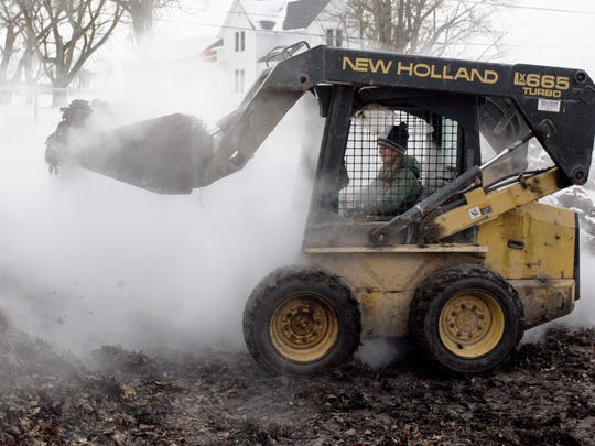 Stephanie Bartel operates a front end loader by the composite pile at Old Plank Farm in Plymouth.