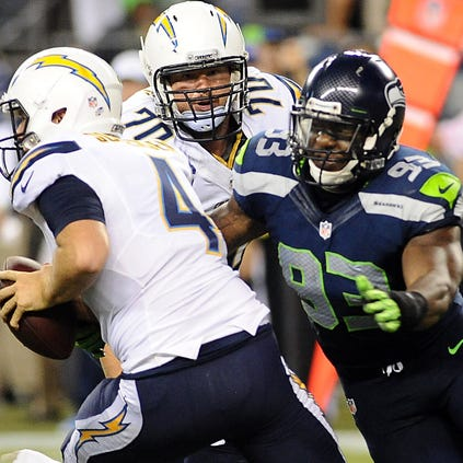 Aug 15, 2014; Seattle, WA, USA; San Diego Chargers quarterback Brad Sorensen (4) is sacked by Seattle Seahawks defensive end O'Brien Schofield (93)  during the second half at CenturyLink Field. The Seahawks beat Chargers 41-14. Mandatory Credit: James Snook-USA TODAY Sports
