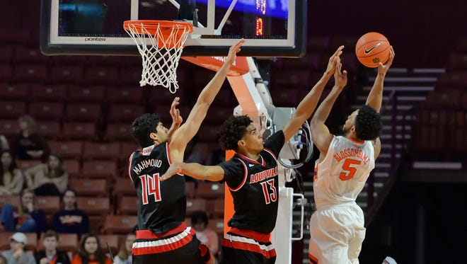 Clemson's Jarod Blossomgame shoots while defended by Louisville's Raymond Spalding (13) and Anas Mahmoud during the first half of an NCAA college basketball game Sunday, Jan. 10, 2016, in Greenville, S.C. (AP Photo/Richard Shiro)