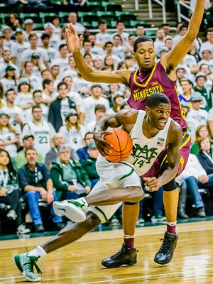 Eron Harris ,14, of MSU cuts from the baseline into the paint in front of Dupree McBrayer of Minnesota during their game Wednesday January 11, 2017 in East Lansing.  KEVIN W. FOWLER PHOTO