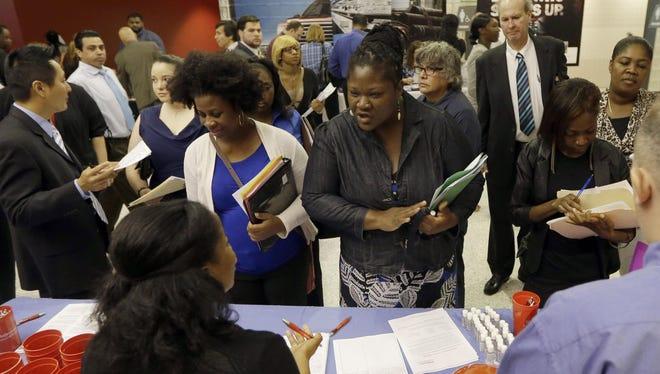 In this photo taken in June, job seekers attend a job fair in Sunrise, Fla.