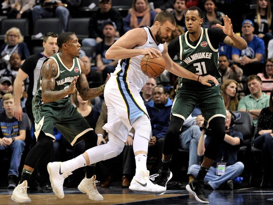 Memphis Grizzlies center Marc Gasol, center, drives