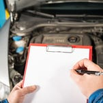 Butch Taylor does a visual inspection of a vehicle's catalytic converter and its exhaust system. Vehicle inspections, no longer required in South Carolina, check major safety systems.