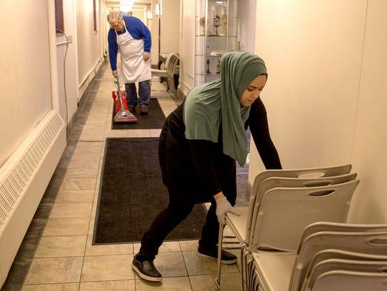 Mark LoPatin vacuums as Shereen Abunada stacks chairs