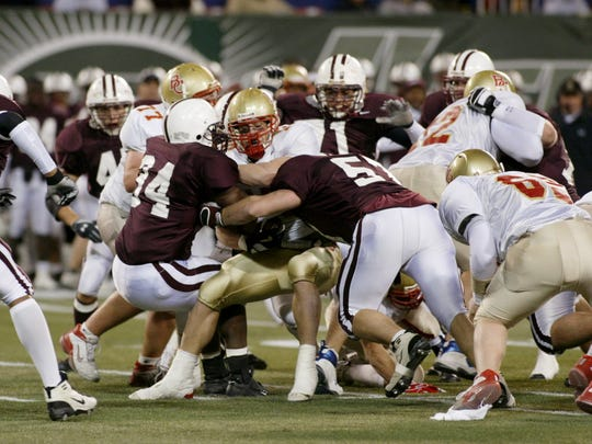 From 2004: Bergen Catholic #10 Brian Cushing is swarmed by Don Bosco defenders during Non-Public Group 4 State Championship high school football action at Giants Stadium.