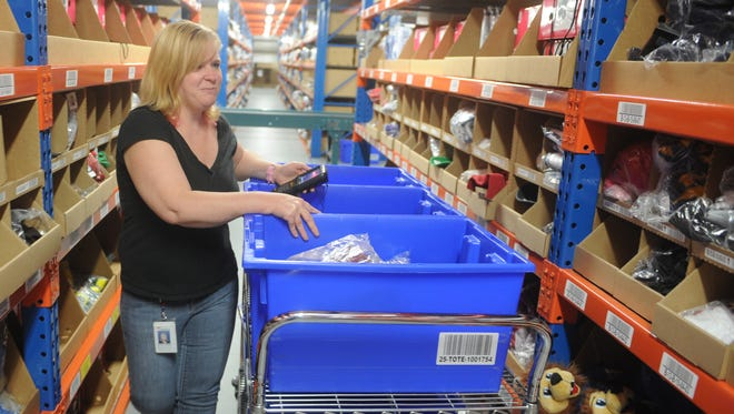 Alicia Copeland of Frazeysburg pulls products from the shelves at Fanatics in Frazeysburg. Fanatics is looking to hire about 1,500 temporary employees.