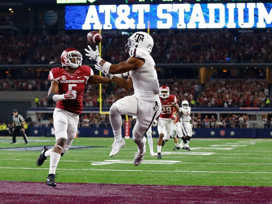 Texas A&M Aggies receiver Christian Kirk (3) catches a pass for a touchdown in overtime against Arkansas Razorbacks cornerback Henre' Toliver (5) at AT&T Stadium. Texas A&M won 28-21 in overtime.