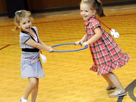Two young girls play during some free time at the gym