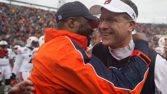 Auburn head coach Gus Malzahn, right, embraces wide