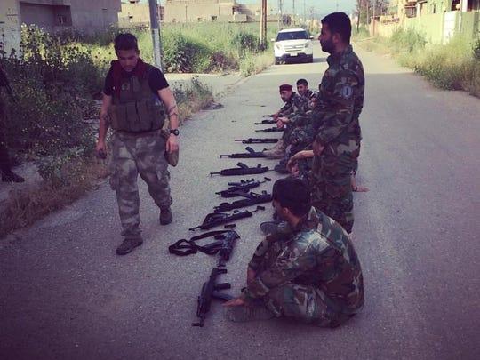Thomas Murawsky, left, trains a militia in Iraq.
