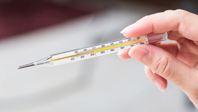 Close-up hand holding on thermometer for checking patient.