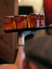A server carries a tray of beer.