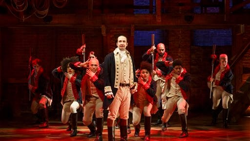 """In this image released by The Public Theater, Lin-Manuel Miranda, center, performs in the musical """"Hamilton"""" at The Public Theater in New York."""