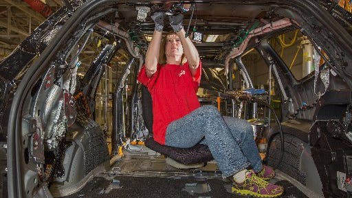 General Motors  worker LeAnn Franke connects wire harnesses to a 2014 Chevrolet Traverse at GM's Lansing Delta Township assembly plant.