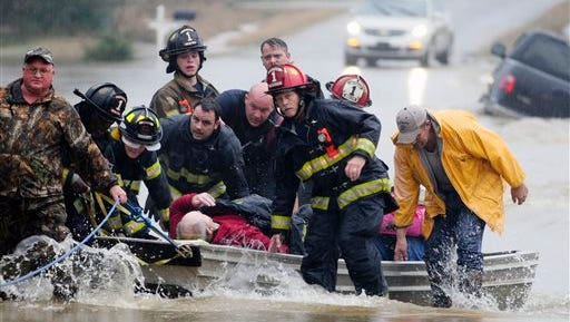 Emergency officials transport James Simmons by boat because water over Byler Road prevented them from reaching him in Moulton, Ala., Friday, Dec. 25, 2015. They carried him by boat before loading him into an ambulance. Unseasonably warm weather helped spawn severe storms Friday after violent storms in the Southeast left dozens of families homeless by Christmas Eve.