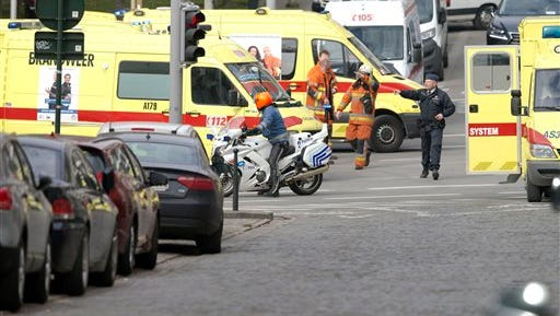 Police direct emergency services after a explosion in a main metro station in Brussels on Tuesday, March 22, 2016. Explosions rocked the Brussels airport and the subway system Tuesday, killing at least 13 people and injuring many others just days after the main suspect in the November Paris attacks was arrested in the city, police said.