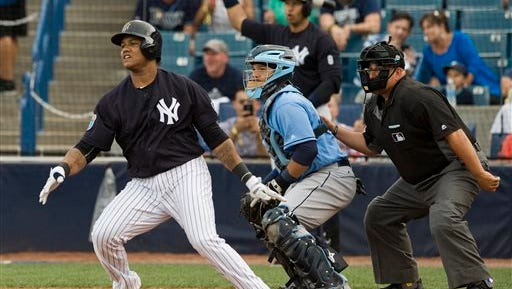 Tampa Bay Rays catcher Rene Rivera, center, and umpire Eric Cooper look on as New York Yankees' Starlin Castro singles during the first inning of a spring training baseball game Thursday, March 24, 2016, in Tampa, Fla.